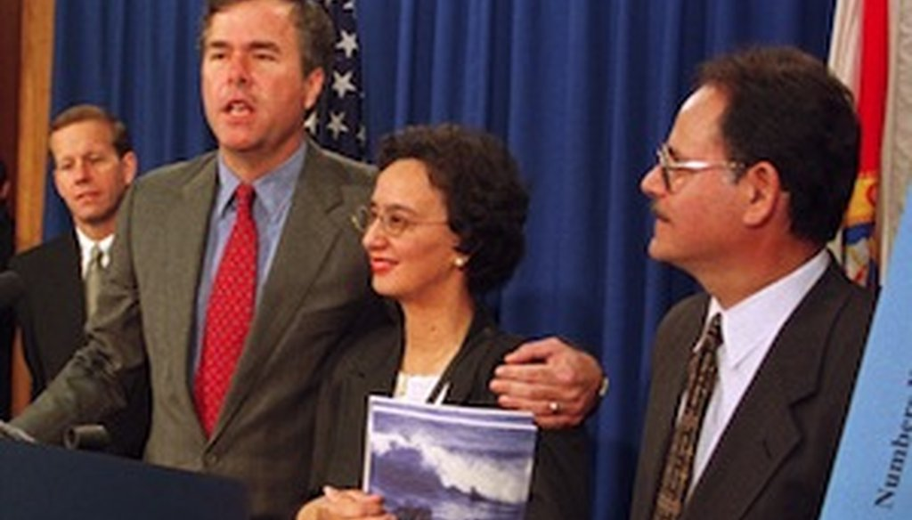 Then Gov. Jeb Bush placed his arm around Berthy De La Rosa-Aponte at a press conference in 1999. (Miami Herald photo)