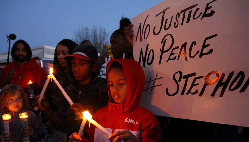 Children light candles at a vigil for Stephon Clark in South Sacramento. Andrew Nixon / Capital Public Radio