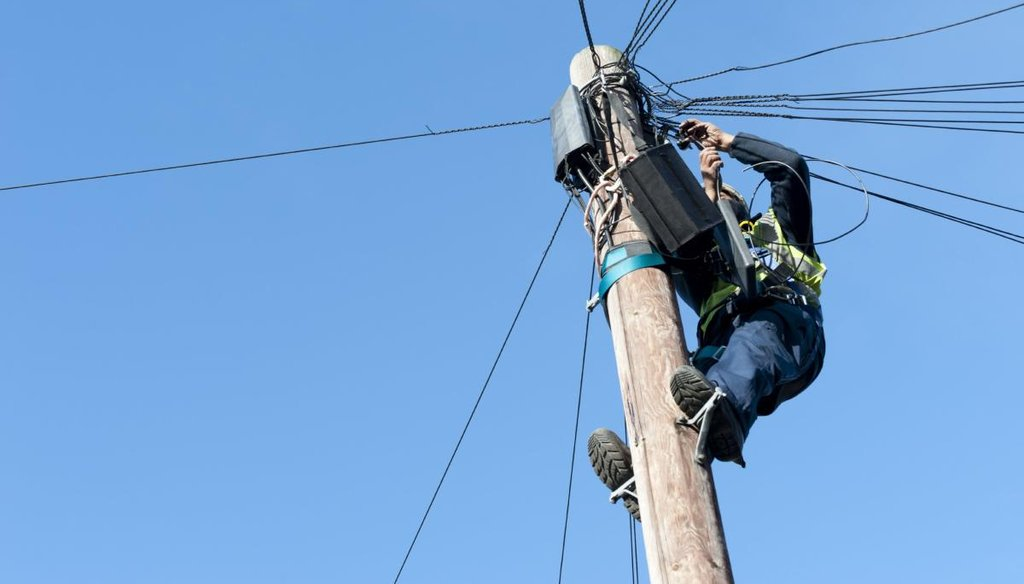 Man installing telephone and broadband cables on a telgraph pole.
