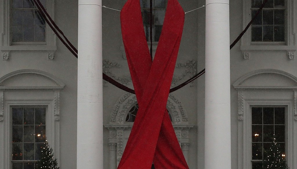 A red ribbon is displayed on the North Portico of the White House to recognize World AIDS Day, December 1, 2015. Photo by Getty Images