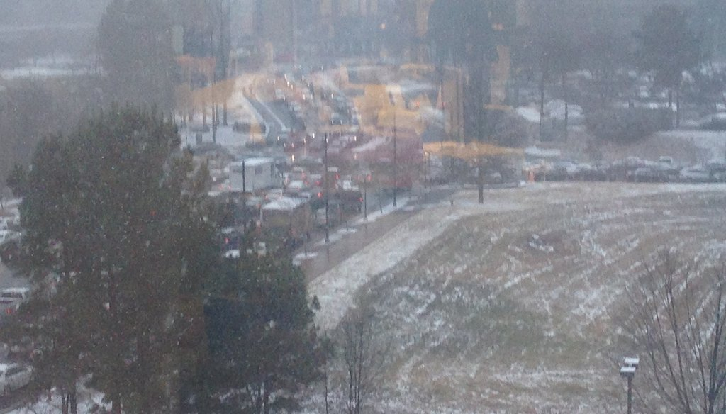 "Traffic was snarled near Perimeter Mall as snow fell upon the Atlanta region Tuesday afternoon. A state official initially said the roads were not ""terrible"" by 3 p.m. Photo credit: Eric Stirgus/AJC."