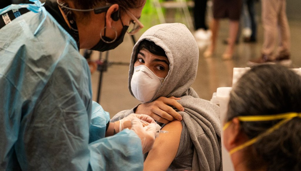 A student looks back at his mother as he is vaccinated at a COVID-19 vaccination clinic for students 12 and older in May 2021 in San Pedro, Calif. (AP Photo/Damian Dovarganes, File)