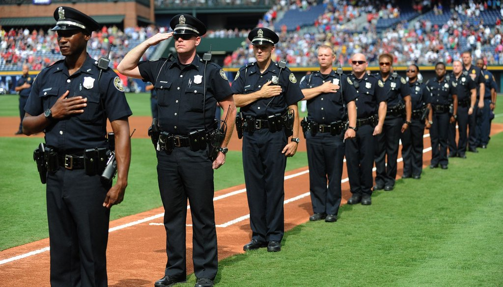 Atlanta police officers pay their respects during a memorial of the Sept. 11, 2001 terrorist attacks. Mayor Kasim Reed and police say an increase in the number of officers hired has contributed to a drop in felony crimes.