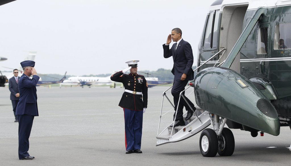 President Barack Obama salutes as he is greeted by Col. Mark Camerer, the 436th Airlift Wing Commander, left, as he steps off of Marine One, at Dover Air Force Base, Del., on Aug. 9, 2011. (AP)
