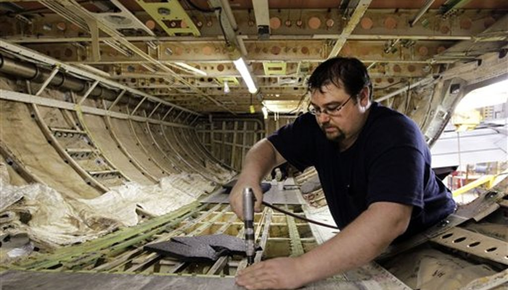 Chris Book, who was accepted into a sheet-metal apprentice program, performs maintenance work on the floor in the cargo hold of a Boeing 737. (AP)