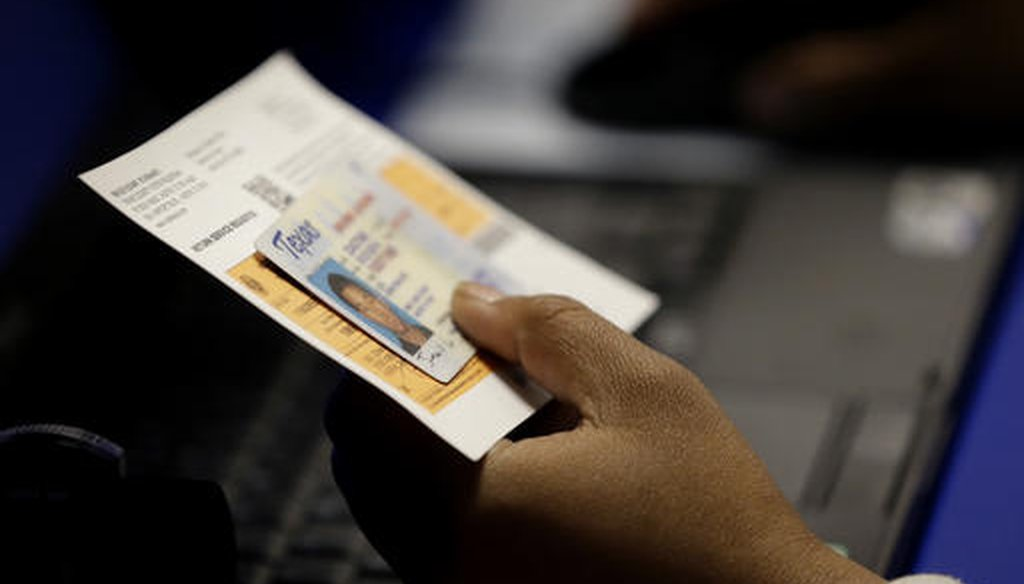 An election official checks a voter's photo identification at an early voting polling site in Austin, Texas, in this 2014 file photo. (AP/Eric Gay)