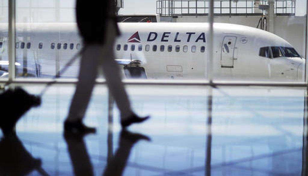 In this Thursday, Oct. 13, 2016, photo, a Delta Air Lines jet sits at a gate at Hartsfield-Jackson Atlanta International Airport in Atlanta. (AP Photo/David Goldman)
