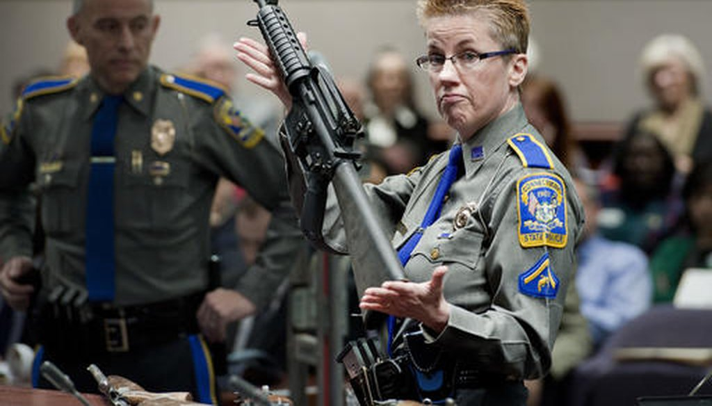 Firearms training unit Detective Barbara J. Mattson, of the Connecticut State Police, holds up a Bushmaster AR-15 rifle Jan. 28, 2013. (AP Photo/Jessica Hill, File)