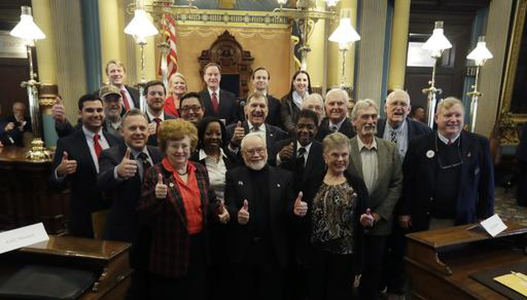 Presidential electors and state officials in Michigan pose in the state senate chamber after voting, on Dec. 19, 2016, in Lansing. (AP)