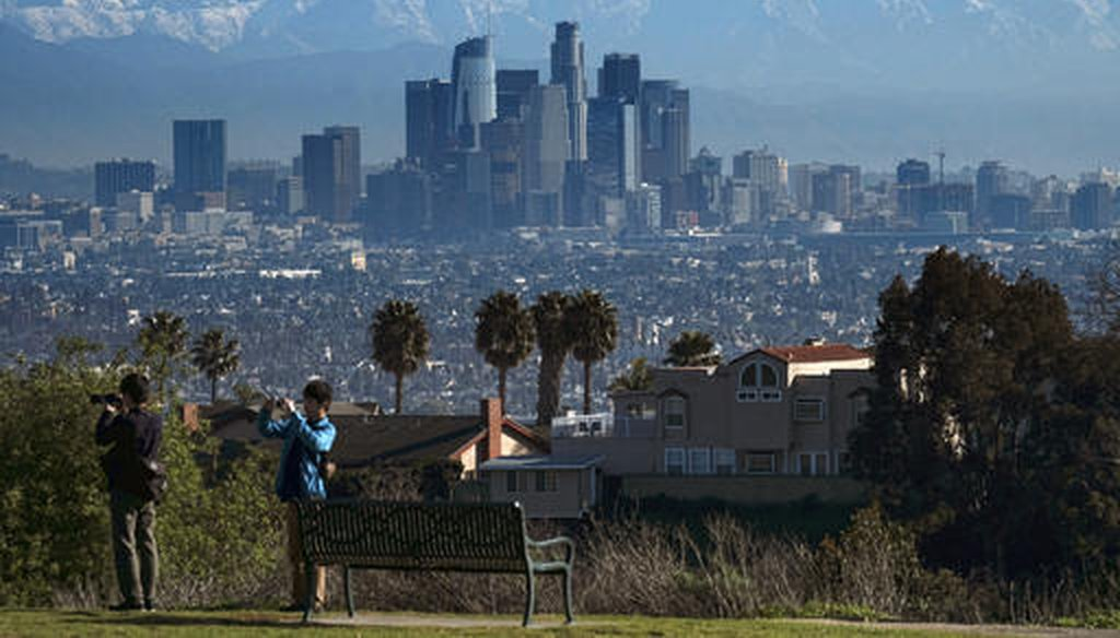 Tourists take photographs as snow covered mountain tops rise behind downtown Los Angeles from Kenneth Hahn State Recreation Area in Los Angeles on Jan. 25, 2017. (AP/Vogel)