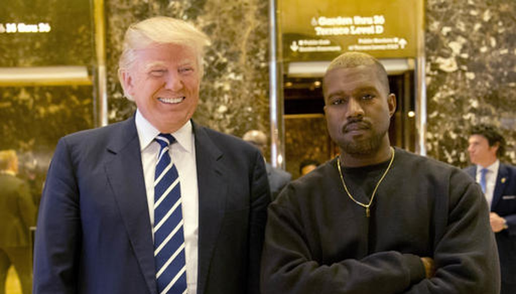 Donald Trump, then the president-elect, poses with Kanye West in the lobby of Trump Tower in New York on Dec. 13, 2016. (AP/Seth Wenig)