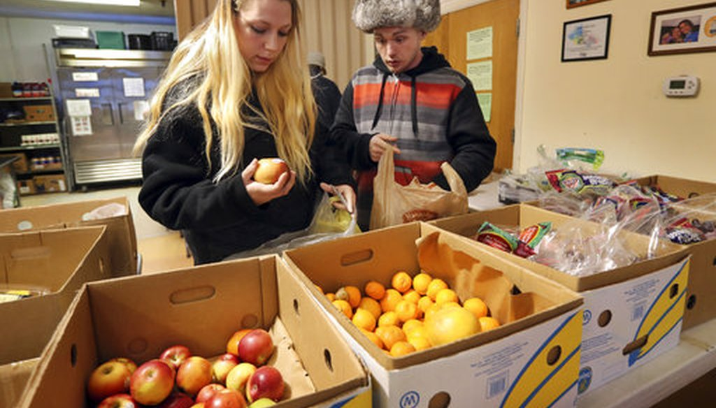 Sunny Larson, left, and Zak McCutcheon pick produce while gathering provisions to take home at the Augusta Food Bank in Augusta, Maine, on March 27, 2017. (AP/Robert F. Bukaty)