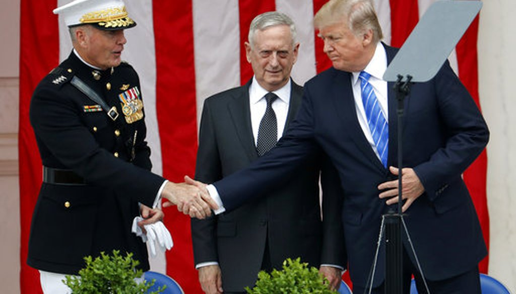 President Donald Trump, right, shakes hands with Joint Chiefs Chairman Gen. Joseph Dunford, left, as Defense Secretary Jim Mattis, center, watches at Arlington National Cemetery on May 29, 2017. (AP)