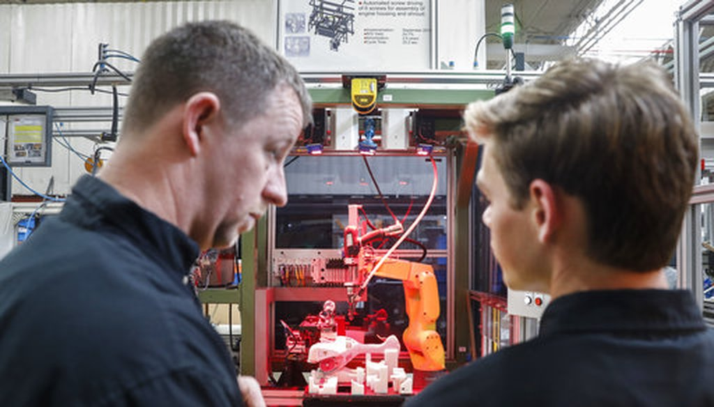 A.J. Scherman, 37, left, works with fellow apprentice Ryan Buzzy, 18, right, on a robotics control computer at a chainsaw assembly line at a Stihl Inc. production plant in Virginia Beach, Va., on May 25, 2017. (AP Photo/John Minchillo)