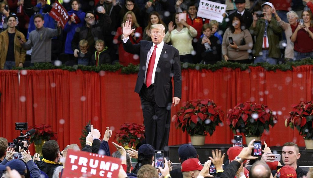 President Donald Trump waves to supporters during a rally in Pensacola, Fla., Dec. 8, 2017, as fake snow falls after his speech. (AP)