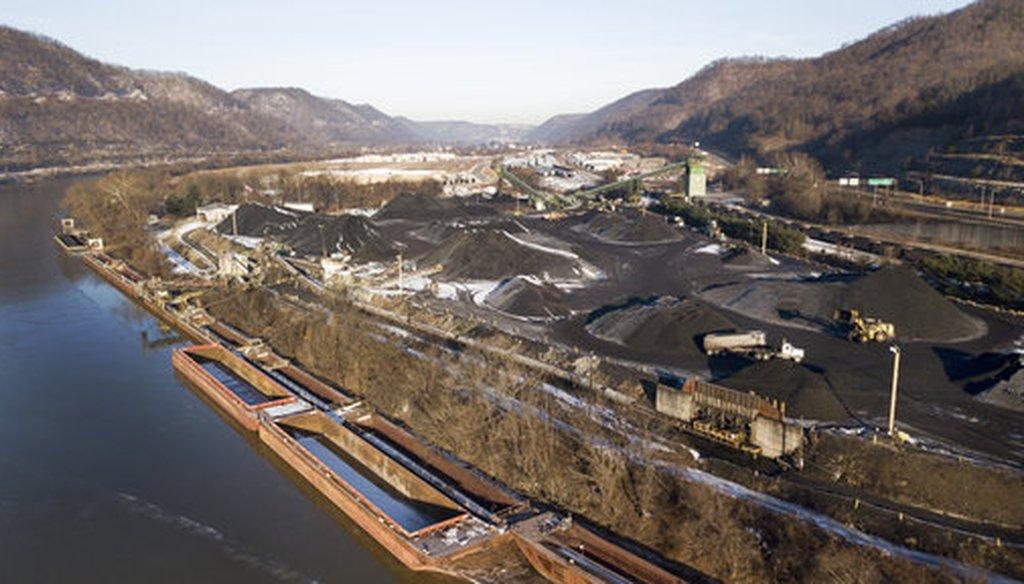 Heavy equipment and trucks move coal in the Sun Coal Co. coal yard along the Kanawha River in Dickenson, W.Va., on Jan. 19, 2018. (AP/Steve Helber)