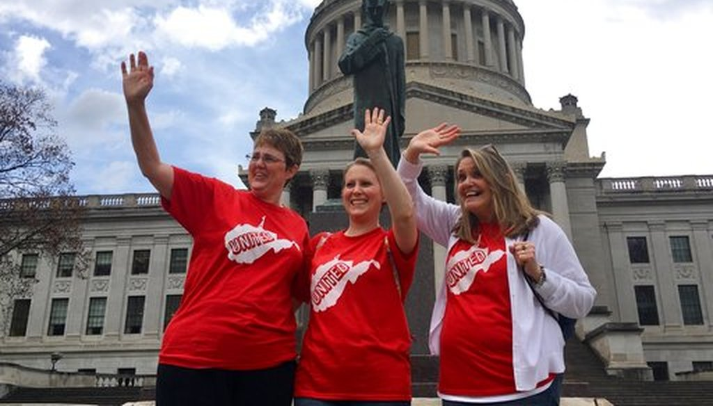 Striking teachers Michelle Myers,left, Holly O'Neil, center, and Suzanne Varner of McNinch Primary School in Moundville, W.Va., wave to passing cars outside the state capitol in Charleston, W.Va, on Feb. 23, 2018. (AP)