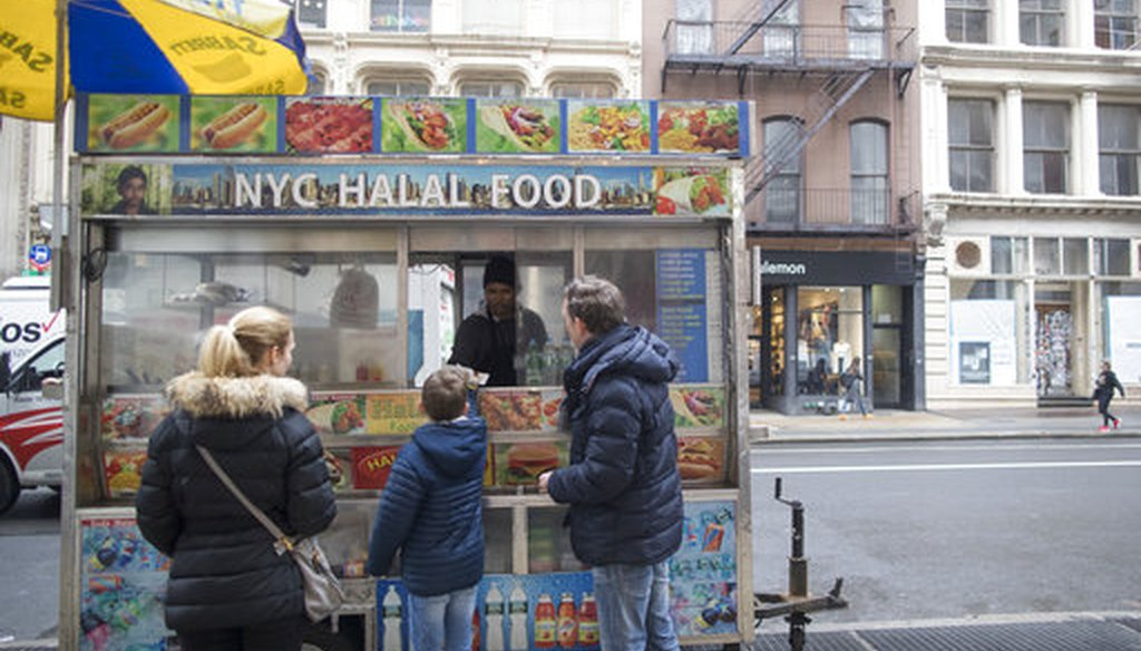 In this Wednesday, April 4, 2018 photo, a family buys hot dogs from a street vendor on Broadway in the Soho neighborhood of New York. (AP Photo/Mary Altaffer)