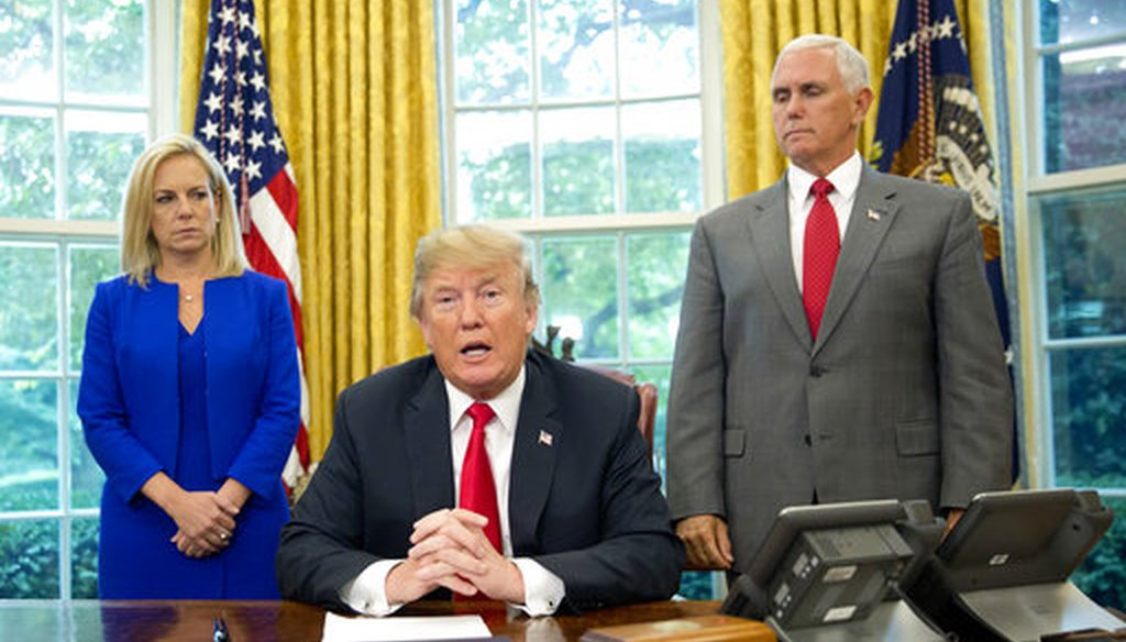 President Donald Trump with Homeland Security Secretary Kirstjen Nielsen and Vice President Mike Pence, signs an executive order to end family separations. (AP Photo/Pablo Martinez Monsivais)