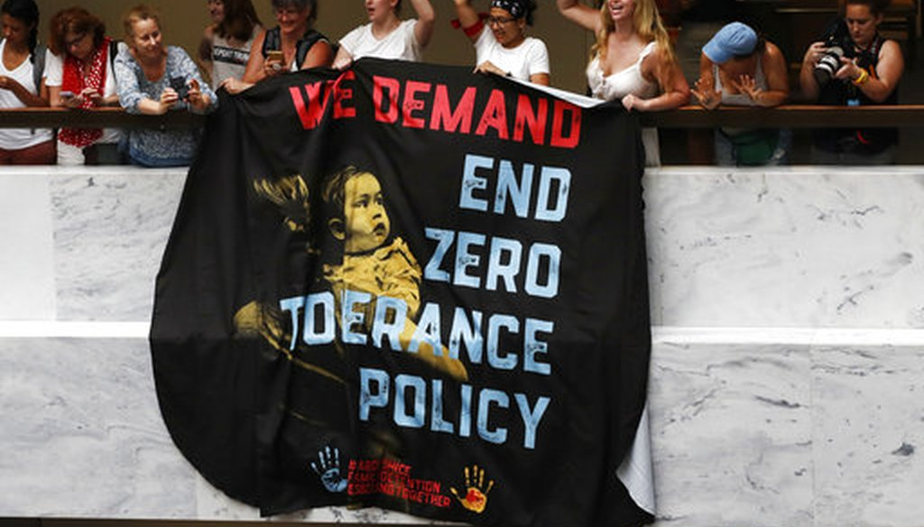 "Women hold a sign that says ""we demand end zero tolerance policy,"" in a hallway during a protest of the separation of immigrant families June 28, 2018, on Capitol Hill in Washington. (AP Photo/Jacquelyn Martin)"