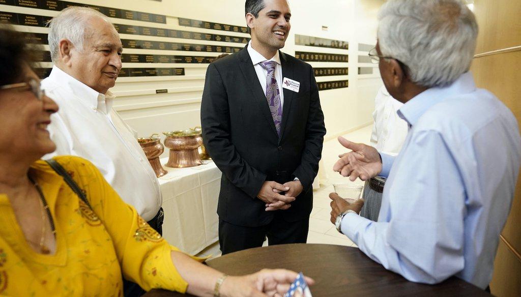 Democrat for Congress candidate Sri Kulkarni, center, listens to supporters attending a fundraiser for him. (AP)