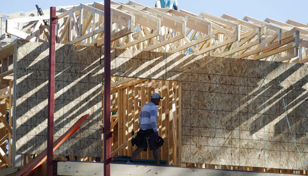 Workers toil on a new home under construction. (AP/David Zalubowski)