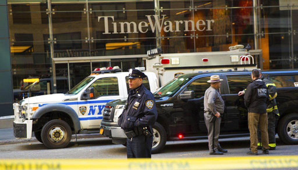 An officer keeps watch in front of the Time Warner Building, where NYPD personnel removed an explosive device Wednesday, Oct. 24, 2018, in New York. (AP Photo/Kevin Hagen)