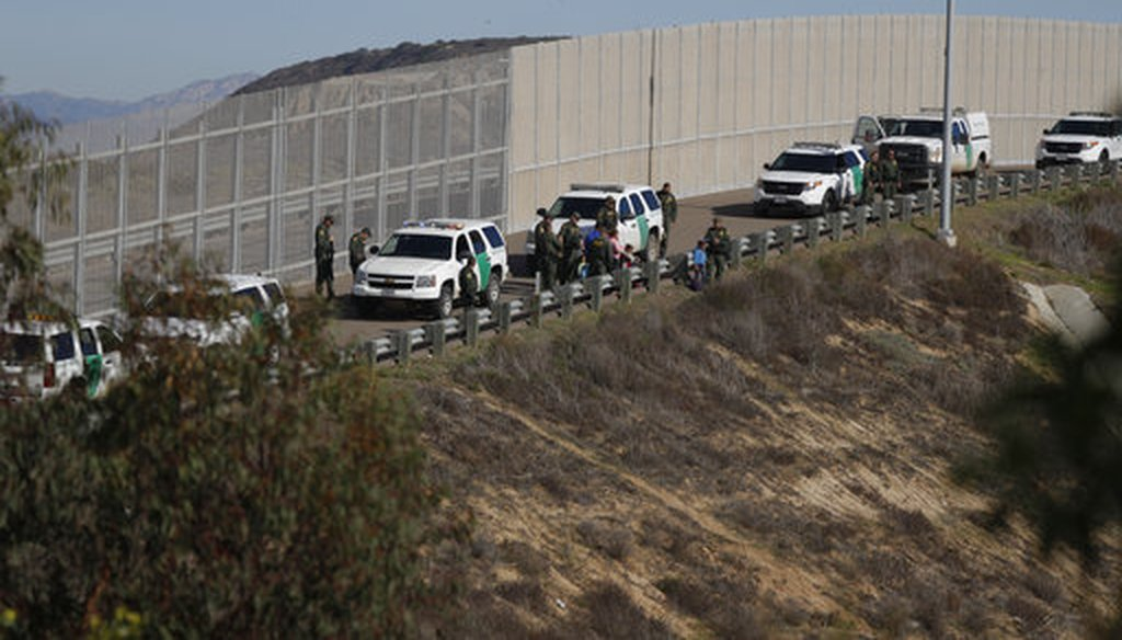 A woman and children stand amidst U.S. Border Patrol agents after crossing illegally over the border wall into San Diego, California, as seen from Tijuana, Mexico, Sunday, Dec. 9, 2018. (AP Photo/Rebecca Blackwell)