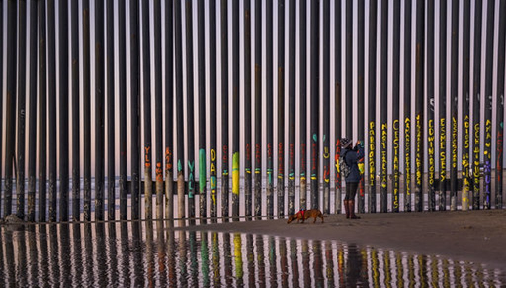 A woman takes a snapshot by the border fence between San Diego, Calif., and Tijuana, as seen from Mexico, on Jan. 3, 2019. (AP/Daniel Ochoa de Olza)