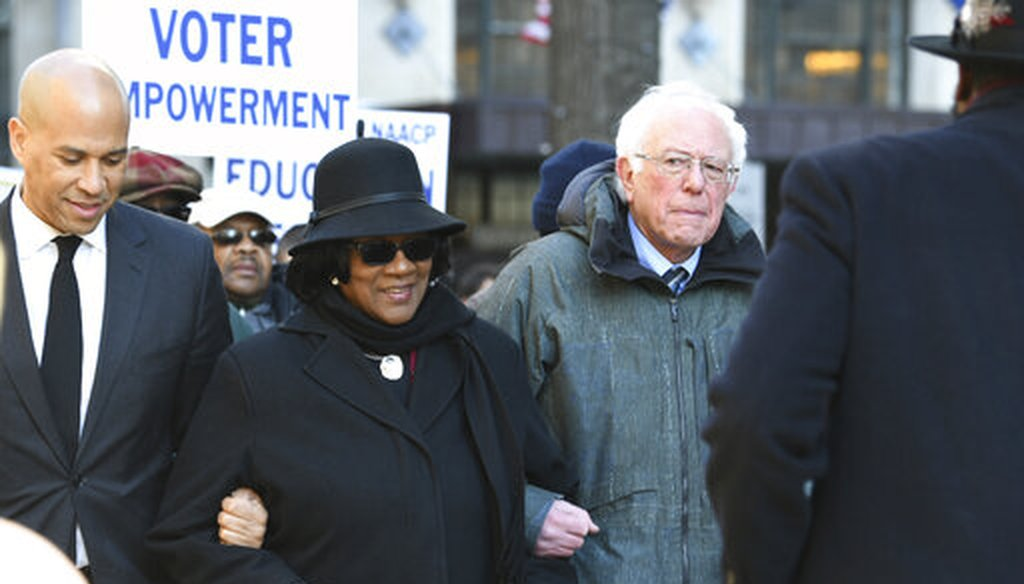 Sen. Cory Booker, D-N.J., left, and Sen. Bernie Sanders, I-Vt., right, march with NAACP President Brenda Murphy Jan. 21, 2019, march in Columbia, S.C. (AP Photo)