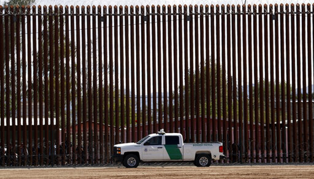 In this April 5, 2019, file photo, a U.S. Customs and Border Protection vehicle sits near the barrier as President Donald Trump visits a new section of the border fence with Mexico in Calexico. (AP/Jacquelyn Martin)