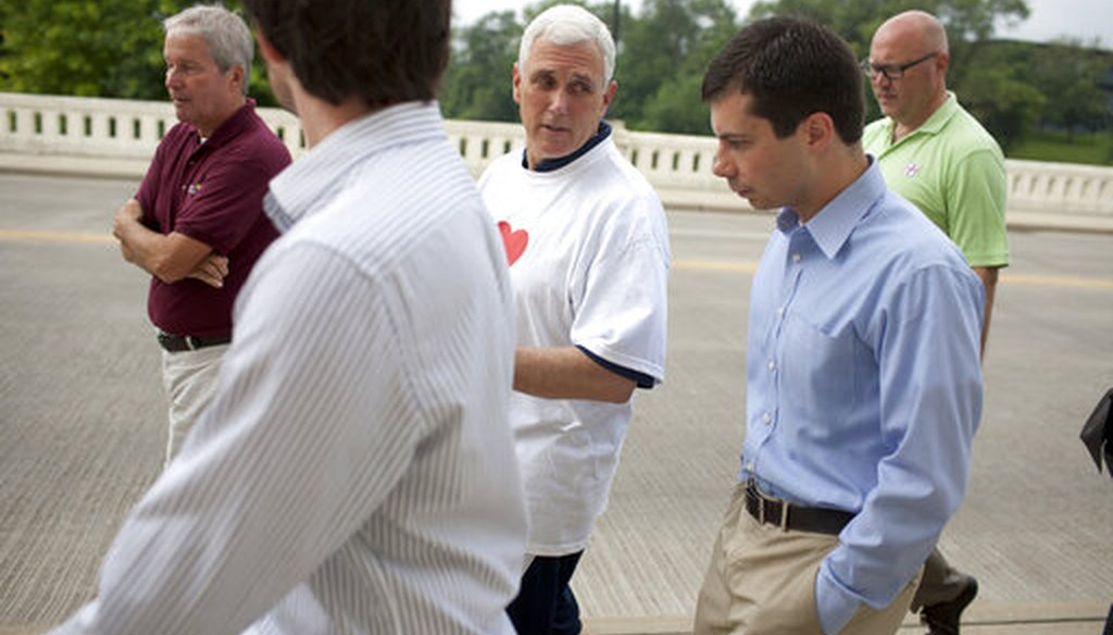 Then-Indiana Gov. Mike Pence, center, talks with South Bend, Ind., Mayor Pete Buttigieg, right, as they cross the Jefferson Boulevard bridge during a fitness walk along the St. Joseph River in South Bend on July 3, 2013. (AP)