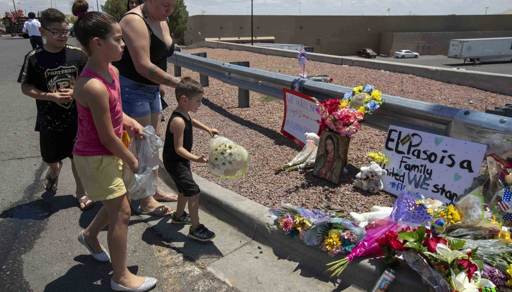 An El Paso family bring flowers to the makeshift memorial for the victims of Saturday mass shooting at a shopping complex in El Paso, Texas, Sunday, August 4, 2019. (AP Photo/Andres Leighton)