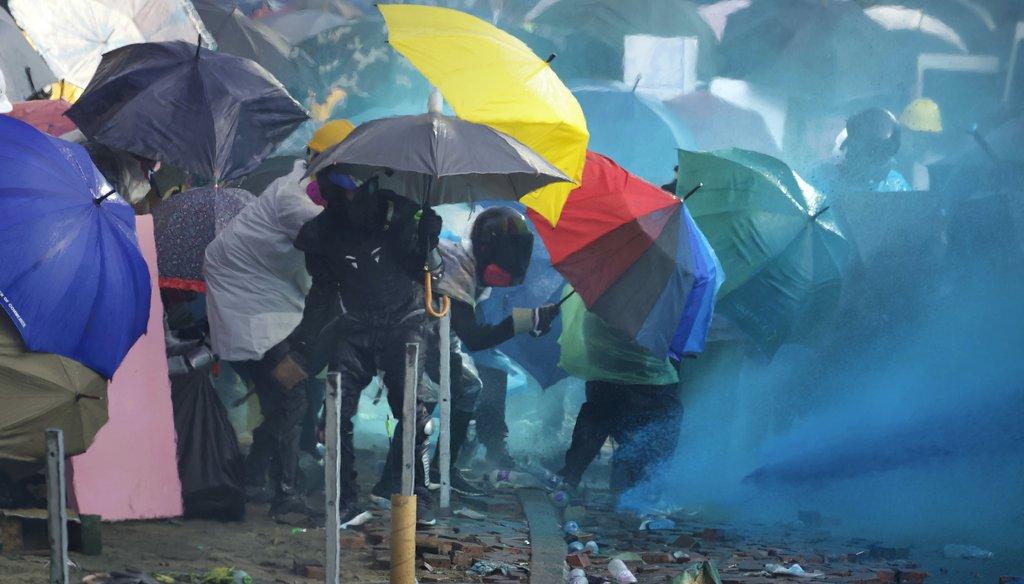 Hong Kong police spray blue-dyed liquid at protesters. (AP)