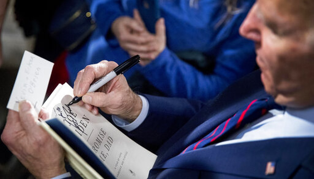 """Democratic presidential candidate Joe Biden signs a copy of his book """"Promise Me, Dad"""" at a campaign rally Jan. 5, 2020, in Davenport, Iowa. (AP)"""