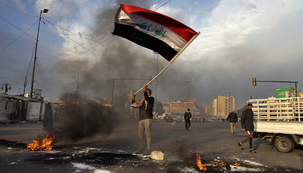 A protester waves the national flag while demonstrators set fire to close streets near Tahrir Square during a demonstration against the Iranian missile strike in Baghdad, Iraq on Jan. 8, 2020. (AP)
