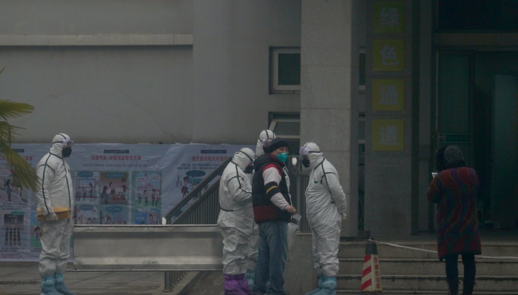 Staff in biohazard suits hold a metal stretcher by the in-patient department of Wuhan Medical Treatment Center, where some infected with a novel coronavirus are being treated, in Wuhan, China on Jan. 21, 2020. (AP)