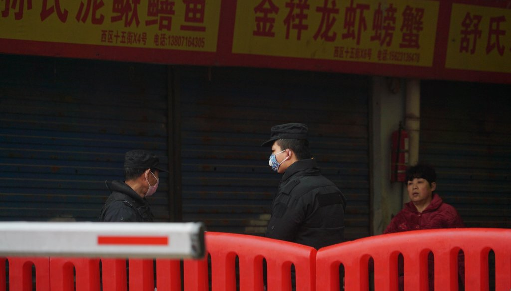 Police stand guard outside Wuhan Huanan Wholesale Seafood Market, where a number of people related to the market fell ill with a virus in Wuhan, China, on Jan. 21, 2020. (AP)