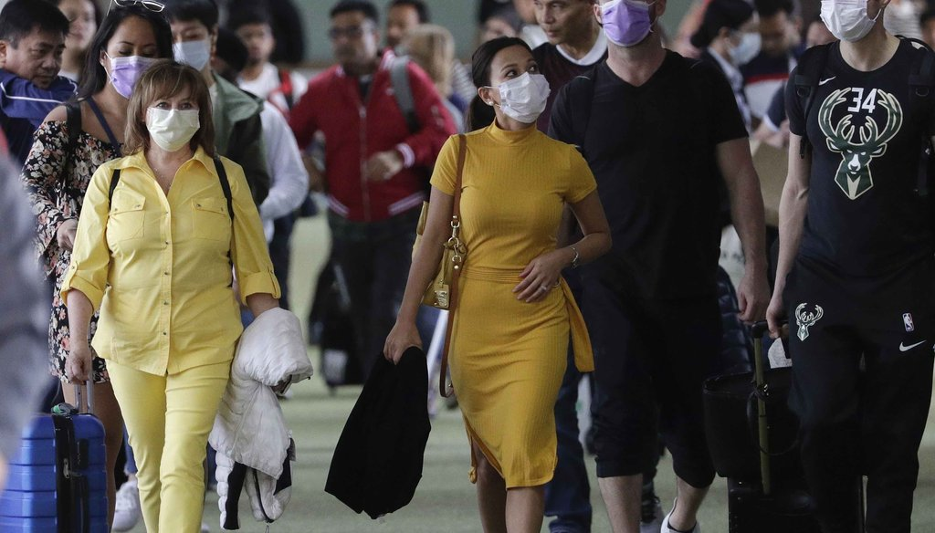 Passengers wear masks as they arrive at Manila's international airport, Philippines, on Jan. 23, 2020. (AP)