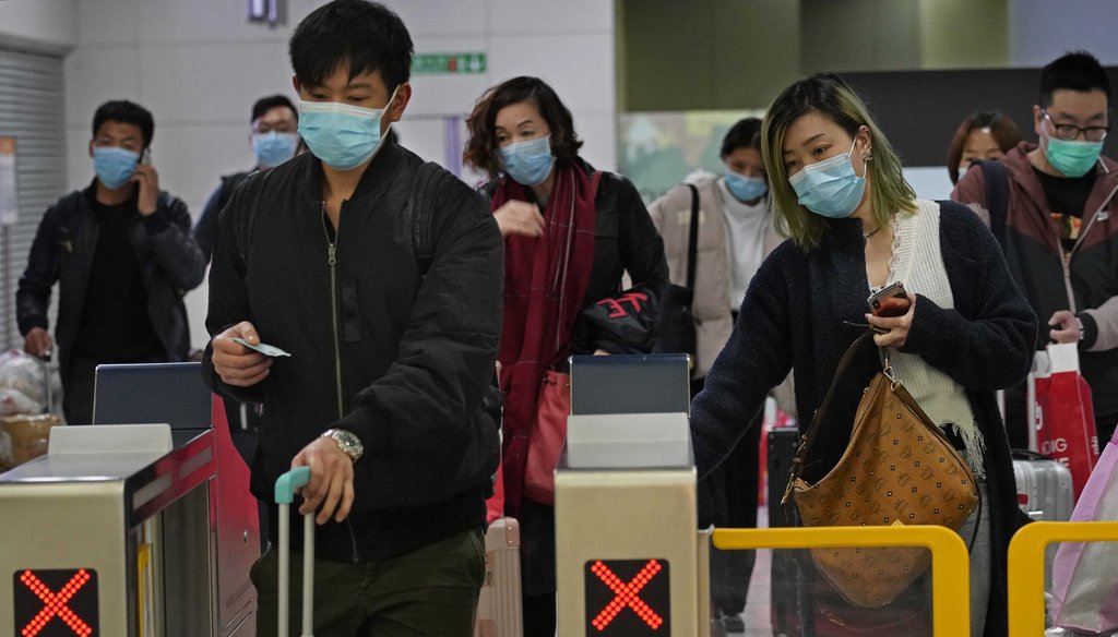 Passengers wear protective face masks arrive at the high speed train station in Hong Kong on Jan. 28, 2020. (AP)