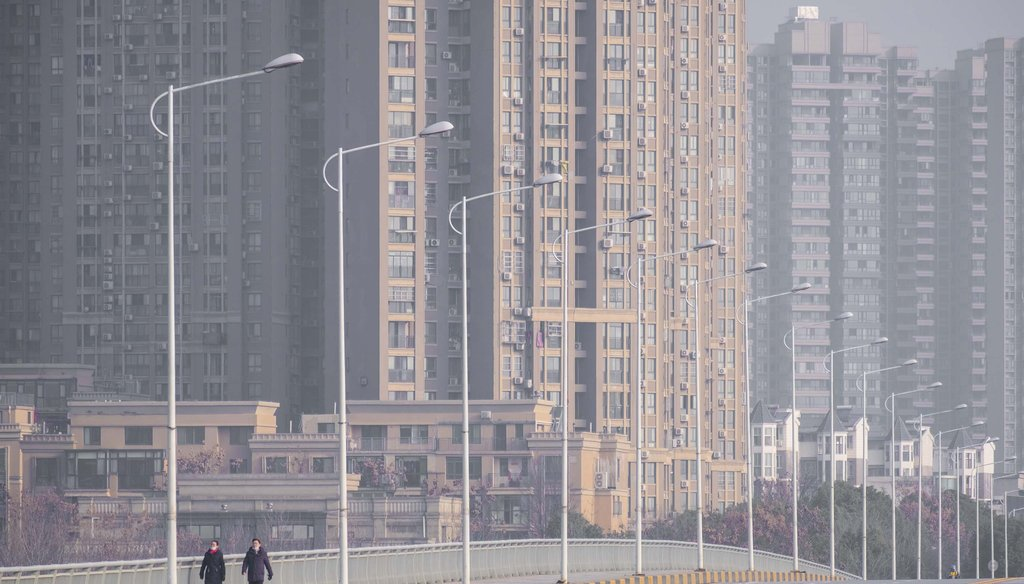 In this Jan. 28, 2020 file photo, people wearing face masks walk down a deserted street in Wuhan in central China's Hubei Province. (AP)