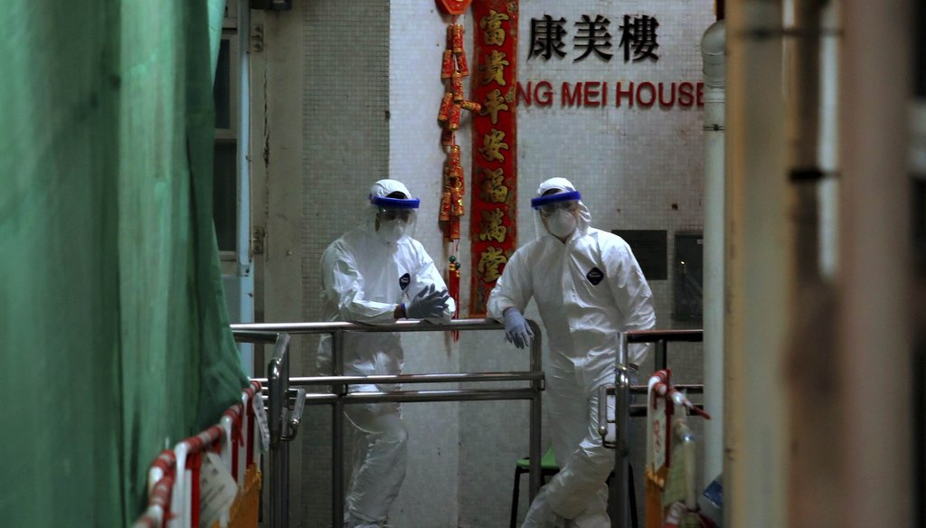 Personnels wearing protective suits wait near an entrance at the Cheung Hong Estate, a public housing estate during evacuation of residents in Hong Kong on Feb. 11, 2020. (AP)