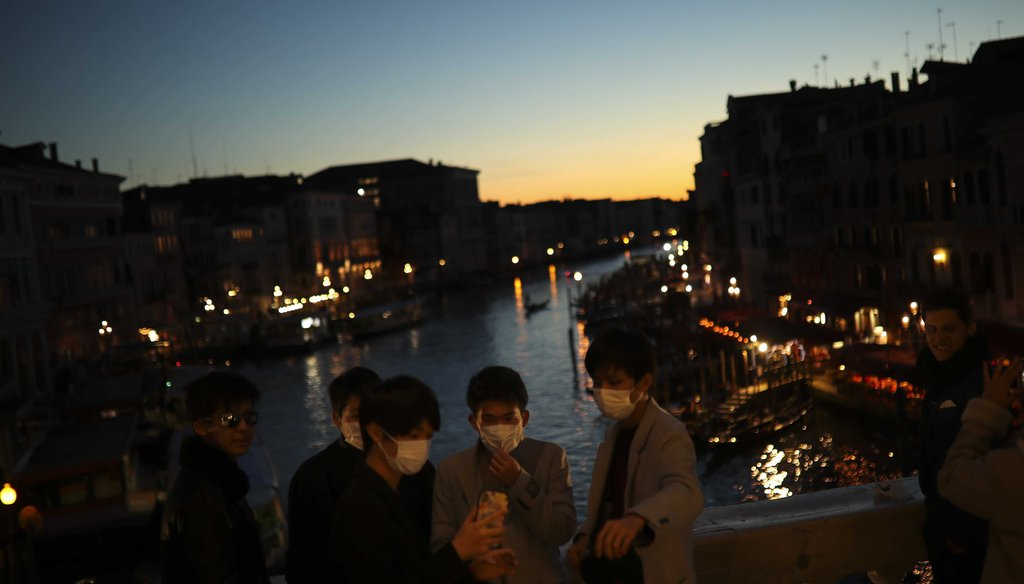 Tourists wearing protective masks pose for a photograph at the Rialto bridge as the sun sets in Venice, Italy, on Feb. 28, 2020. (AP)