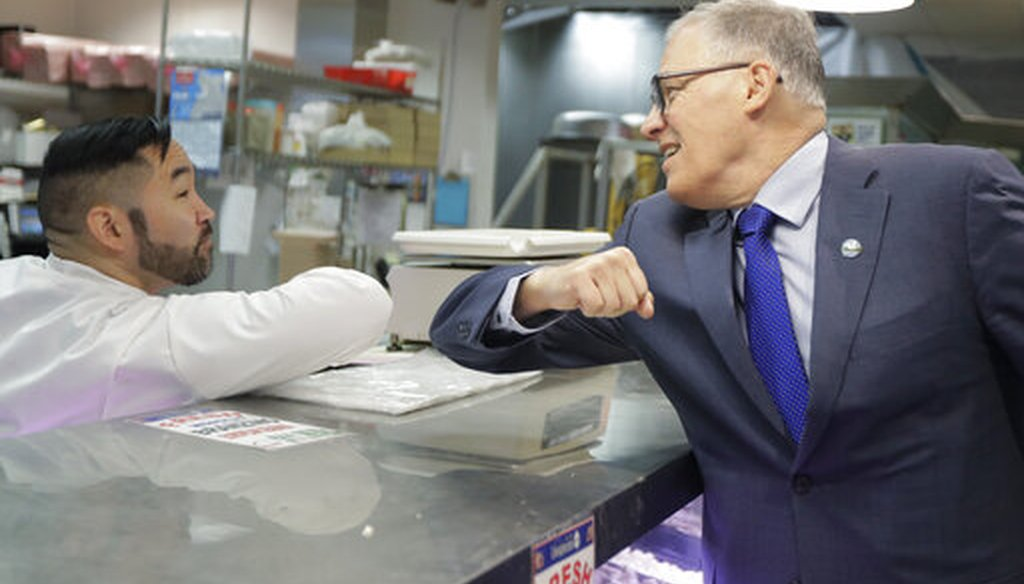 Washington Gov. Jay Inslee, right, greets a worker at the seafood counter of the Uwajimaya Asian Food and Gift Market on March 3, 2020. (AP)
