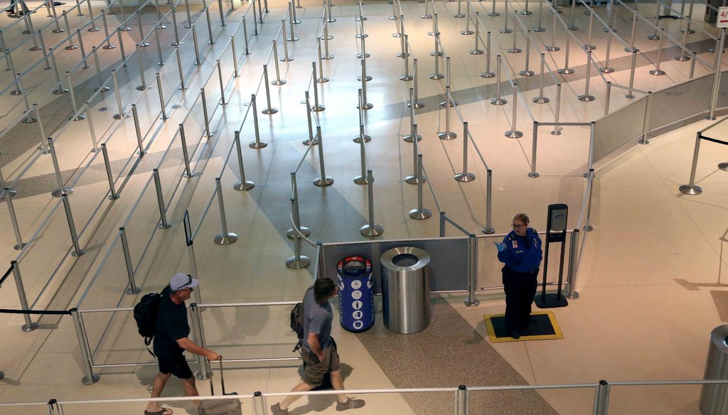 A TSA agent speaks to travelers passing through an empty security queue at Love Field airport in Dallas on March 12, 2020, amid concerns of the coronavirus pandemic. (AP)
