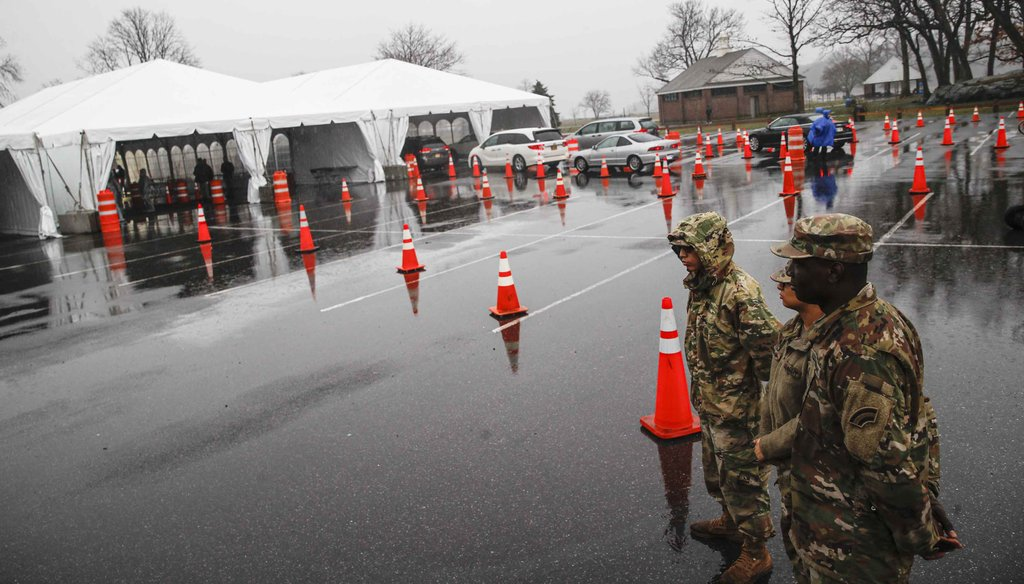 National Guard personnel stand beside a line of motorists waiting for COVID-19 coronavirus infection testing at Glen Island Park in New Rochelle, N.Y., on March 13, 2020, (AP)