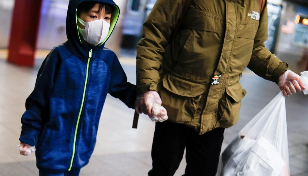 A child wears a protective mask and gloves in the subway system due to COVID-19 concerns, Thursday, March 19, 2020, in New York. (AP)
