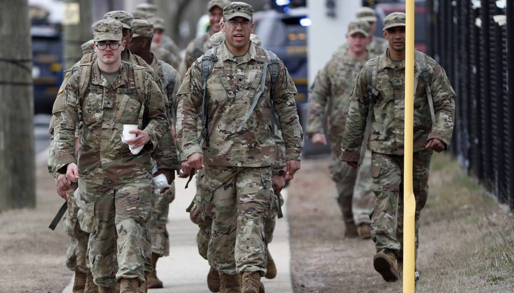 National Guard personnel march in formation as they leave duty after working on March 19, 2020, at a state-managed coronavirus drive-through testing site that just opened on Staten Island in New York. (AP)