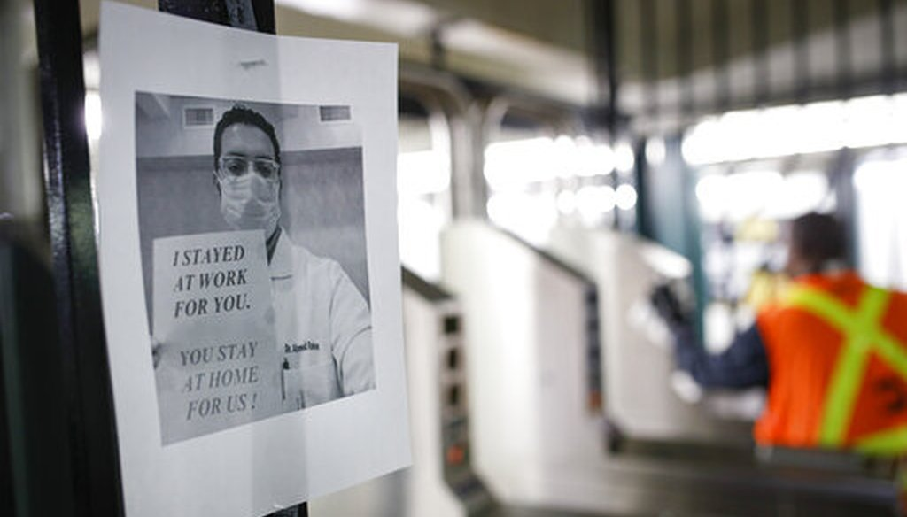 A flier urging customers to remain home hangs at a turnstile as an MTA employee sanitizes surfaces at a subway station on March 20, 2020, in New York City. (AP)