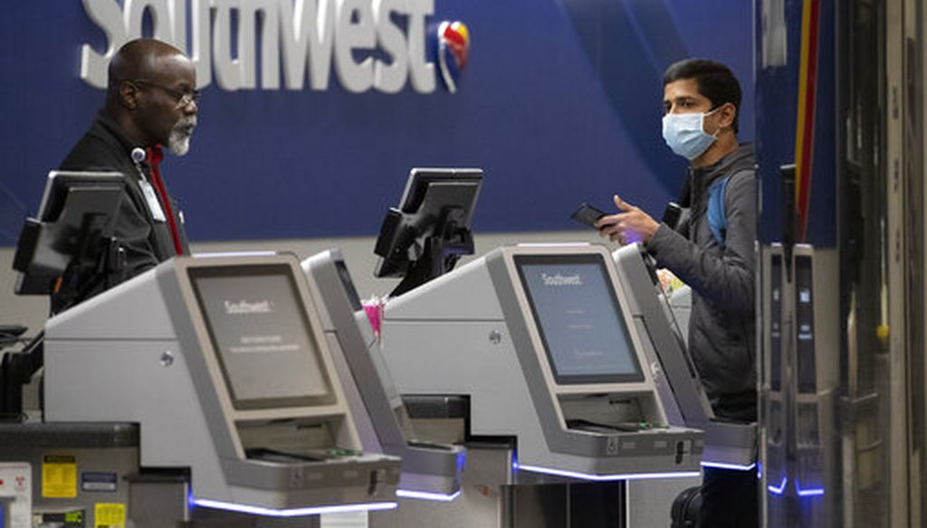 A Southwest Airlines employee helps a passenger wearing a facial mask at LaGuardia Airport on March 21, 2020, in New York, N.Y. (AP)